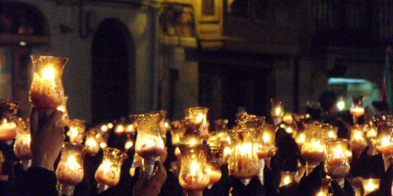 Las hermanas de la cofradía de Jesús Nazareno alzan sus tulipas a la entrada de la Virgen de la Soledad en la tarde-noche del Sábado Santo.